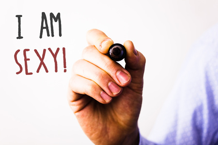 Conceptual hand writing showing I Am Sexy Motivational Call. Business photo texts Feeling of attraction Awareness of beautyMan holding pen pointing idea message black red letters white background