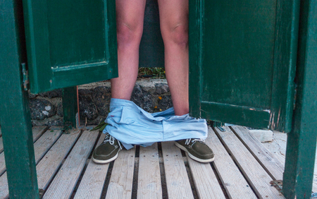 A man standing at the back of the open door. The guy underpants falling down from his legs down to the wooden floor. Stealing the moment photography. Adult teaser image