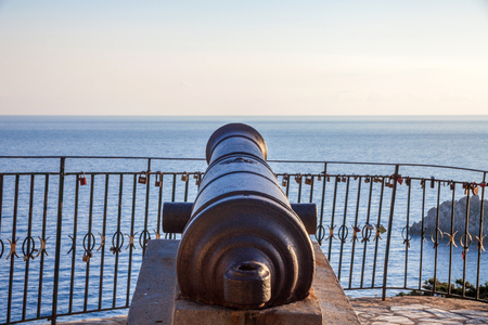 A cannon pointing towards the sea. The ancient artillery sitting above the concrete block. A calm sea surrounds the statue. Revolutionary war machinery