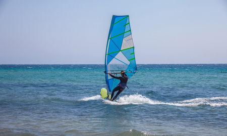 A man balancing the sailing board. Strong waves gliding below the water sport equipment. Windsurfing enthusiast in action. Promoting activity in the beach Stock Photo