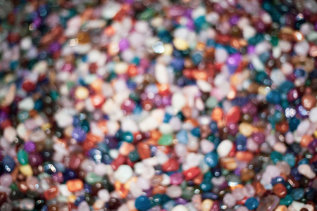 A blurry image of colorful stones. Different kinds of  crystals glittering bright under the shining sun. Beach collectibles and garden beautification accessory Archivio Fotografico