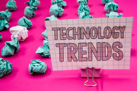 Conceptual hand writing showing Technology Trends. Business photo showcasing Trending Modern Viral Advanced Development Trendy New Paperclip with pink letters pink ground green paper lobs Stock Photo