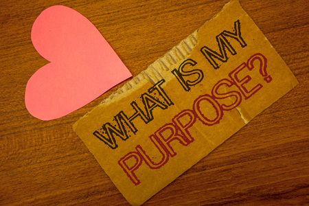Text sign showing What Is My Purpose Question. Conceptual photo Direction Importance Discernment Reflection Peru color torn page with engraved black red text woody desk pink heart