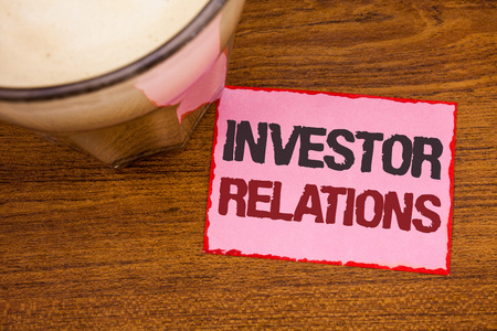 Conceptual hand writing showing Investor Relations. Business photo text Finance Investment Relationship Negotiate Shareholder Wooden desktop red lined pink paper with several texts coffee mug