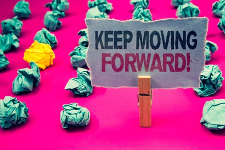 Writing note showing  Keep Moving Forward Motivational Call. Business photo showcasing Optimism Progress Persevere Move Emerald paper balls yellow lump rosy floor paperclip retain grey page