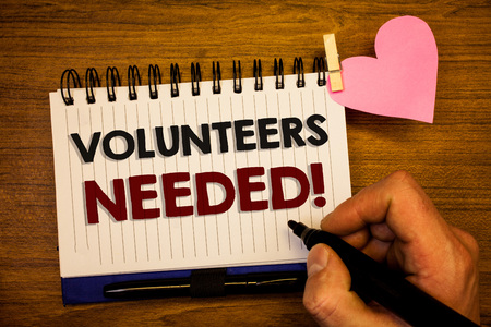 Conceptual hand writing showing Volunteers Needed Motivational Call. Business photo text Social Community Charity Volunteerism Human hand retain black pen notepad with words on paper pink heart
