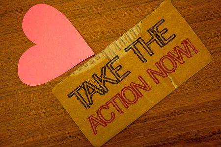 Text sign showing Take The Action Now Motivational Call. Conceptual photo Act Start Promptly Immediate Instantly Peru color torn page with engraved black red text woody desk pink heart