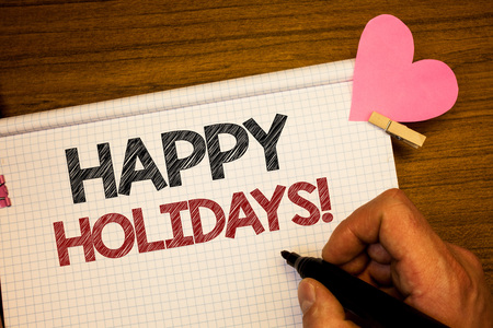 Writing note showing  Happy Holidays Motivational Call. Business photo showcasing Greeting Celebrating Festive Days Man holding pen ideas notebook pink heart letters on wooden background