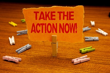 Writing note showing  Take The Action Now Motivational Call. Business photo showcasing Act Start Promptly Immediate Instantly Paperclip holding orange page show red text woody floor with clip