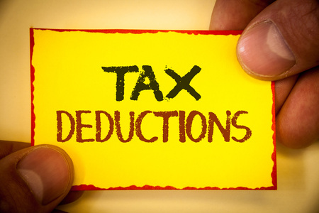 Writing note showing  Tax Deductions. Business photo showcasing Reduction on taxes Investment Savings Money Returns Text Words yellow paper red border fingers holding corner messsage