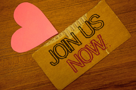 Text sign showing Join Us Now. Conceptual photo enroll community register website Recruit someone Sign-up Peru color torn page with engraved black red text woody desk pink heart