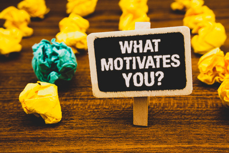 Text sign showing What Motivates You Question. Conceptual photo Passion Drive Incentive Dream Aspiration Blackboard with letters wooden floor blurry yellow paper lumps green lob