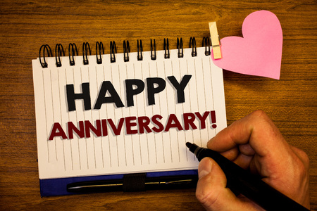 Conceptual hand writing showing Happy Anniversary Motivational Call. Business photo text Annual Special Milestone Commemoration Human hand retain black pen notepad with words on paper pink heart