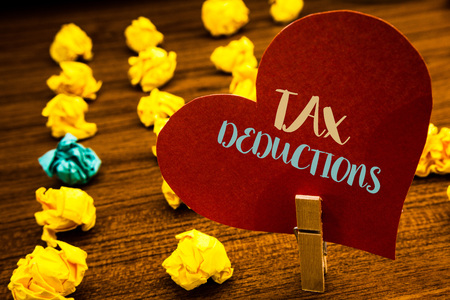 Text sign showing Tax Deductions. Conceptual photo Reduction on taxes Investment Savings Money Returns Text red heart wood clip desk crumbled paper notes yellow blue love message