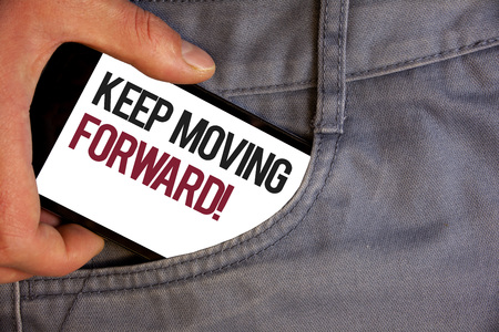 Word writing text Keep Moving Forward Motivational Call. Business concept for Optimism Progress Persevere Move Personage hand pushing mobile phone into back pocket fascinating way