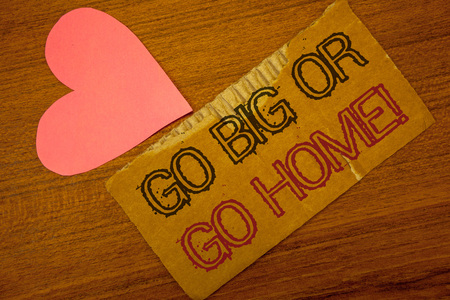Text sign showing Go Big Or Go Home Motivational Call. Conceptual photo Mindset Ambitious Impulse Persistence Peru color torn page with engraved black red text woody desk pink heart