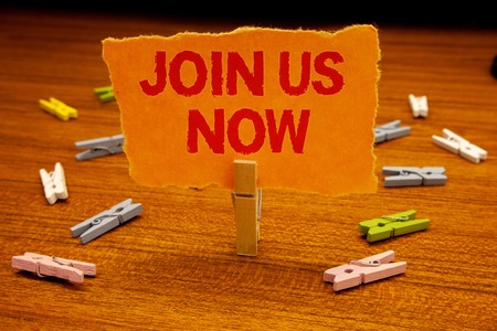 Writing note showing  Join Us Now. Business photo showcasing enroll community register website Recruit someone Sign-up Paperclip holding orange page show red text woody floor with clip Stock Photo