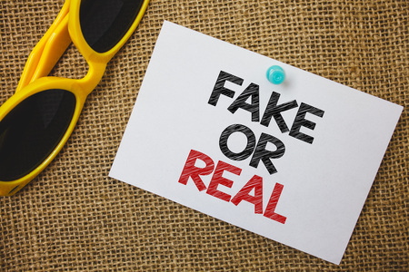 Writing note showing  Fake Or Real. Business photo showcasing checking if products are original or not checking quality Sunglass paper wonderful white background lovely message idea memories Stock Photo