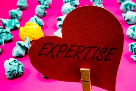 Handwriting text Expertise. Concept meaning Expert skill or knowledge in a particular field Experience Wisdom Clothespin holding red heart paper crumpled papers ideas mistakes trials Stock Photo