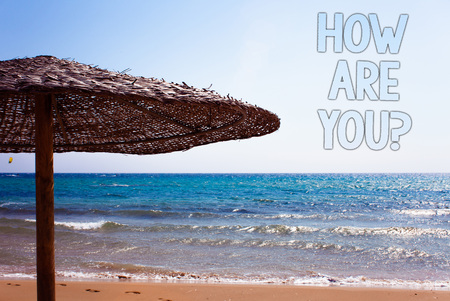Writing note showing  How Are You Question. Business photo showcasing Your Health status Asking about your life and health Blue beach sand message idea sunshade water sky natural landscape
