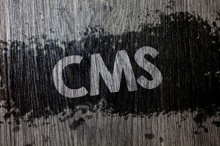 Text sign showing Cms. Conceptual photo Content Management System supports modification of digital content Wooden wood background black splatter paint ideas messages intentions