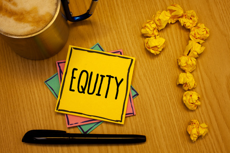 Writing note showing  Equity. Business photo showcasing Value of a company divided into equal parts owned by shareholders Message wood table coffee cup question mark crumpled papers