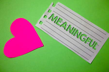 Conceptual hand writing showing Meaningful. Business photo showcasing Having meaning Significant Relevant Important Purposeful Small paper drawing heart green background remember message