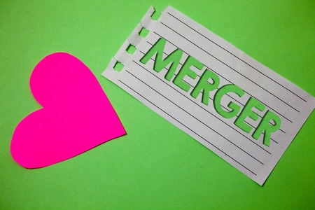 Conceptual hand writing showing Merger. Business photo showcasing Combination of two things or companies Fusion Coalition Unification Small paper drawing heart green background remember message