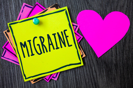 Handwriting text writing Migraine. Concept meaning Recurrent headache in one side of head nausea and disturbed vision Border sticky remember cards love heart pinned dark woody background Imagens