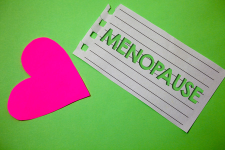 Conceptual hand writing showing Menopause. Business photo showcasing Cessation of menstruation Older women hormonal changes period Small paper drawing heart green background remember message