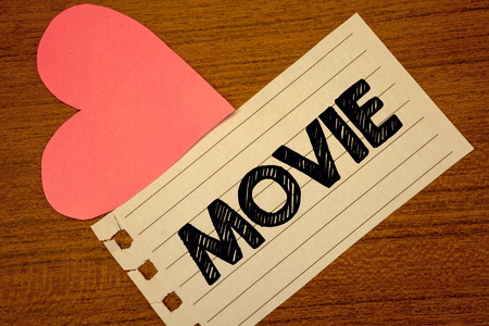 Word writing text Movie. Business concept for Cinema or television film Motion picture Video displayed on screen Paperpiece page heart table background typing job clerk study material Stock Photo