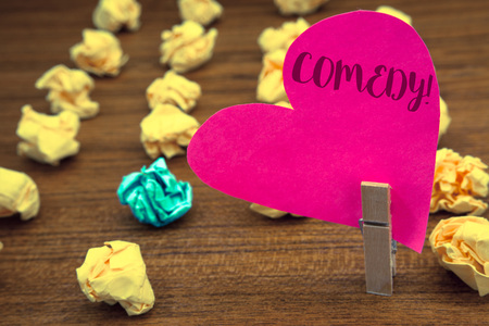 Word writing text Comedy Call. Business concept for Fun Humor Satire Sitcom Hilarity Joking Entertainment Laughing Clothespin holding pink heart paper crumpled papers ideas mistakes trials