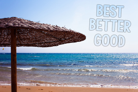 Writing note showing  Best Better Good. Business photo showcasing improve yourself Choosing best choice Deciding Improvement Blue beach sand message idea sunshade water sky natural landscape Stock Photo