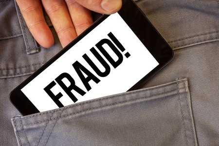 Writing note showing  Fraud Motivational Call. Business photo showcasing Criminal deception to get financial or personal gain Man holding cell phone white screen jean pocket messages application