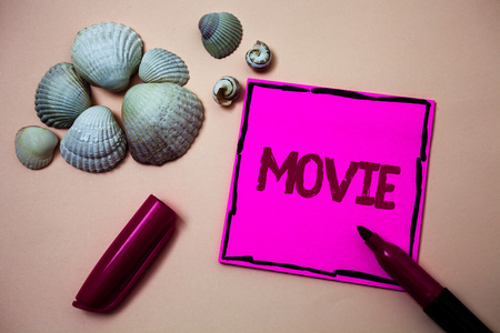 Text sign showing Movie. Conceptual photo Cinema or television film Motion picture Video displayed on screen Ink marker open cap small shells handwrittern notes artwork paper sheet Stock Photo