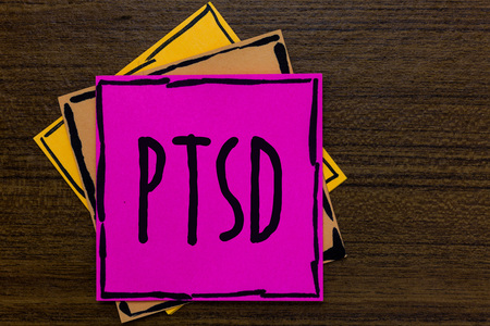 Writing note showing Ptsd. Business photo showcasing Post Traumatic Stress Disorder Mental Illness Trauma Fear Depression Three art small paper two yellow one pink wood brown lite grey shadow