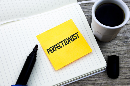 Handwriting text Perfectionist. Concept meaning Person who wants everything to be perfect Highest standards Study material folder card register notebook pen cap tea coffee cup table Stock Photo