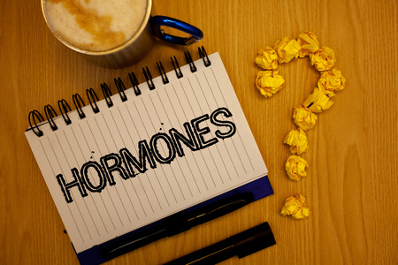 Handwriting text Hormones. Concept meaning Regulatory substance produced in an organism to stimulate cells Ideas grunge notebook coffee cup crumpled papers equal sign wooden wood Stock Photo