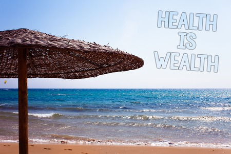 Writing note showing  Health Is Wealth. Business photo showcasing being in good shape great value Stay healthy eat Healthy Blue beach sand message idea sunshade water sky natural landscape