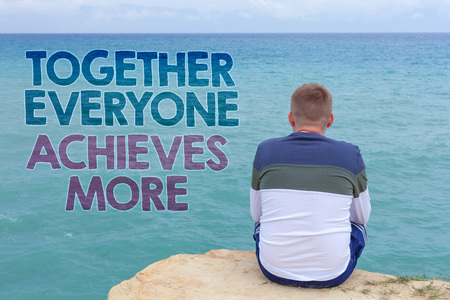 Writing note showing  Together Everyone Achieves More. Business photo showcasing Teamwork Cooperation Attain Acquire Success Man sitting sand watching beach Message Relax reflection intention Reklamní fotografie