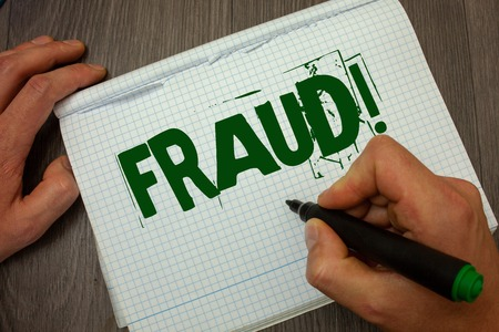 Conceptual hand writing showing Fraud Motivational Call. Business photo text Criminal deception to get financial or personal gain Man hold holding black marker gruge notebook wooden wood table