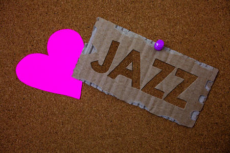 Conceptual hand writing showing Jazz. Business photo text Type of music of black American origin Musical genre Strong rhythm Brown old damaged paperboard ideas pink heart cork background