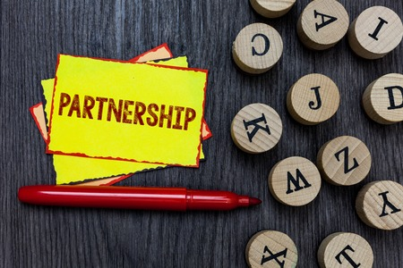 Writing note showing Partnership. Business photo showcasing Association of two or more people as partners Cooperation Unity Multiple small sticky cards wood alphabet button pen grey background Фото со стока