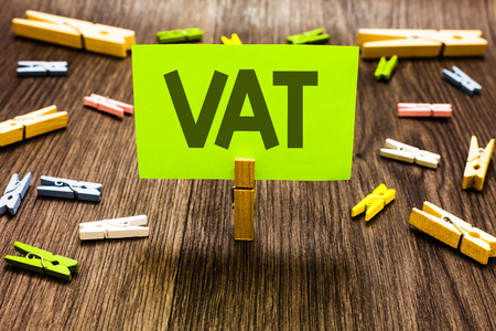 Writing note showing Vat. Business photo showcasing Consumption tax levied on sale barter for properties and services Clips art board creative ideas paper paperclip holding wood shadow