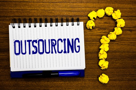 Handwriting text writing Outsourcing. Concept meaning Obtain goods or service by contract from an outside supplier Study notebook register ink pen question mark answer session brown table