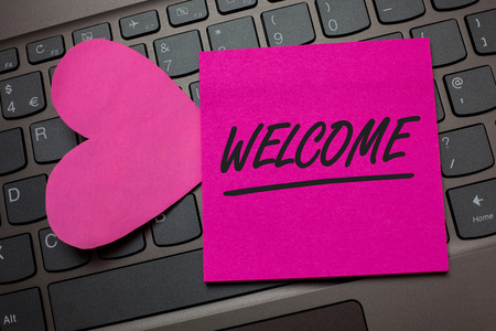 Conceptual hand writing showing Welcome. Business photo text Warm salutation acknowledgement for someone amiable loved thanked Keyboard grey keys pink paper love idea thought computer hart
