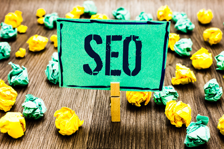Conceptual hand writing showing Seo. Business photo showcasing Search engine optimization increase in online marketing channel Crumpled papers ideas mistakes paperclip clip objects wood Archivio Fotografico