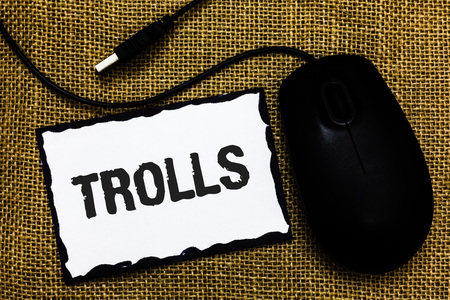 Handwriting text Trolls. Concept meaning Online troublemakers posting provocative inflammatory messages USB black mouse art board paper ideas thoughts ideas designs mat shadow Stock Photo - 104193125