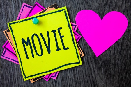 Handwriting text writing Movie. Concept meaning Cinema or television film Motion picture Video displayed on screen Border sticky remember cards love heart pinned dark woody background