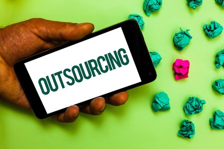 Conceptual hand writing showing Outsourcing. Business photo text Obtain goods or service by contract from an outside supplier Text message smart screen mobile handset crumpled small balls